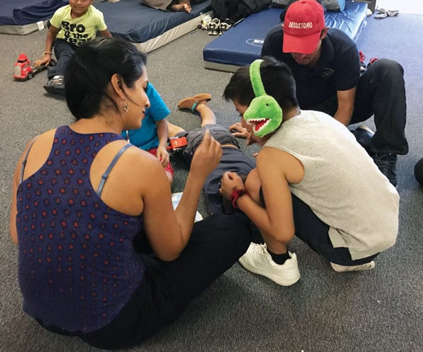 Helena Niño de Guzman, a Wisconsin kindergarten teacher on mission immersion trip, plays with young separated migrants at Loretto-Nazareth Migrant Center in El Paso, Texas. (D. Kelly/U.S.)