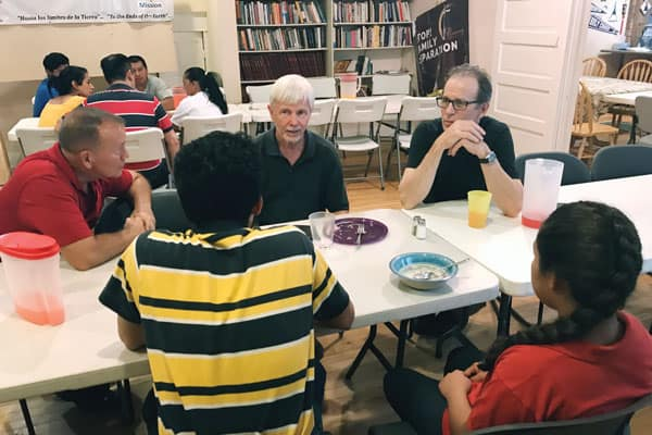 On immersion trip (l. to r.) Chuck Peabody, Scott Wright and Gerry Lee talk with separated migrants reunited at Annunciation House in El Paso. (D. Kelly/U.S.)