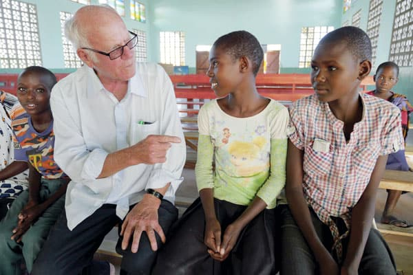 Father Schoellmann chats with children, some of whom are from the Watatulu tribe, in the church he built in Bukundi, Tanzania.