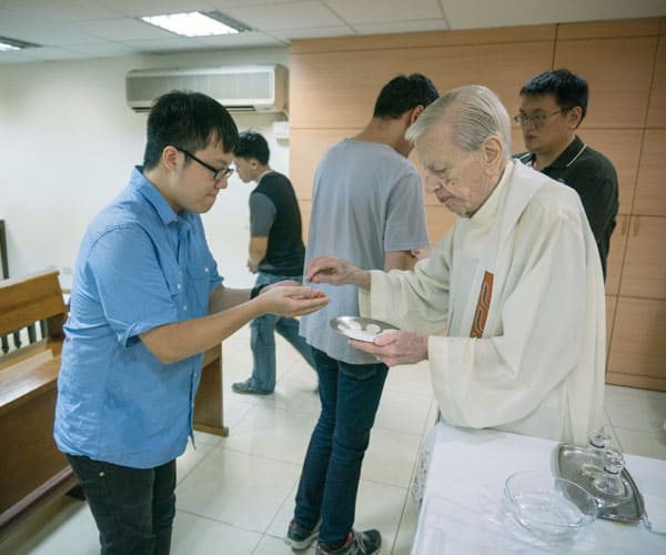 Father Doyle Helps Foster Catholic Friendship and Love in Taiwan: Father Doyle distributes Holy Communion at evening Mass at Friendship House. (Nile Sprague/Taiwan)