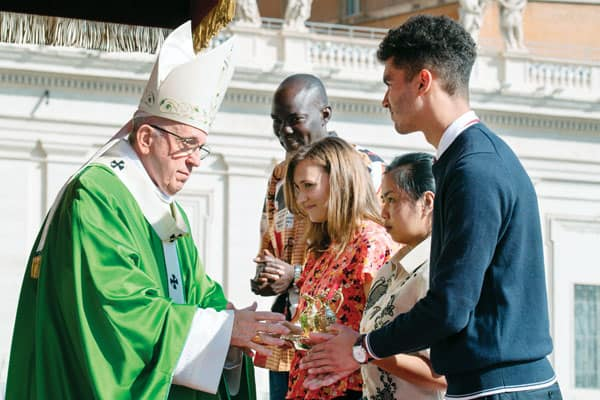 Listening, Discerning, Engaging Youth and Young Adults: Pope Francis accepts the offertory gifts from young people at the opening Mass of the Synod of Bishops last October in St. Peter's Square. (CNS/Vatican Media/Rome)