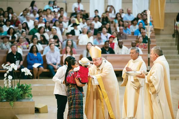Former undocumented immigrant helps migrants today in Los Angeles: Archbishop José H. Gomez of Los Angeles blesses a family from Guatemala at a Mass celebrated in recognition of all immigrants. (Archdiocese of Los Angeles/Victor Aleman)