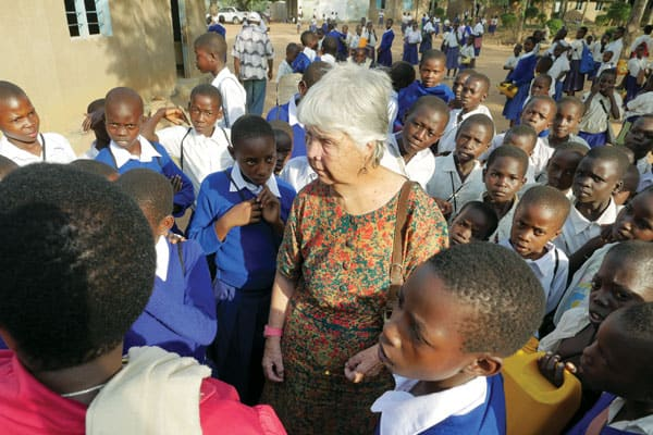 Sister Hughes is surrounded by students she helps outside of Musoma, Tanzania.