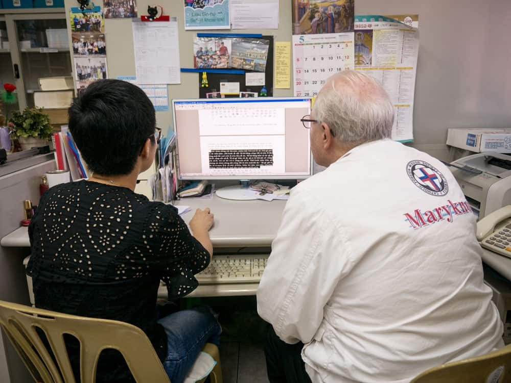 Father Anderson and Isabella Gao review translated texts at the Maryknoll Language Service Center in Taichung, Taiwan. (N. Sprague/Taiwan)