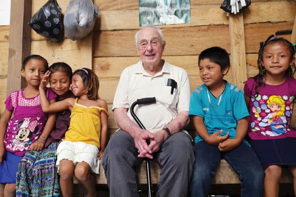 After celebrating Sunday Mass in El Remate village, Father Bill Mullan enjoys chatting with the children in their Q'eqchi' language, which he has mastered over the years. (Sean Sprague)