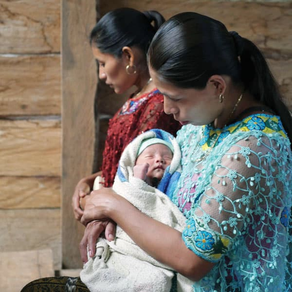 Wearing her native dress, a Q'eqchi' Mayan villager cradles her infant as she prays at Mass. (Sean Sprague)
