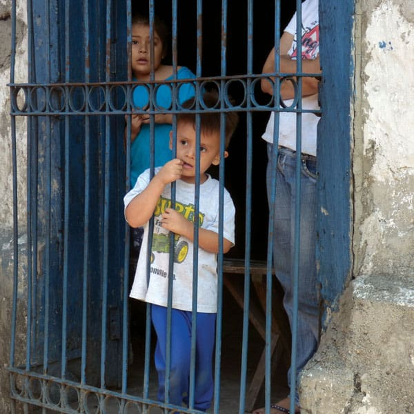 A little boy looks out from the safety of metal bars in front of his house on a Good Friday procession going through the streets of Soyapango, El Salvador. (CNS/R. Guidos/El Salvador) Slug: El Salvador violence