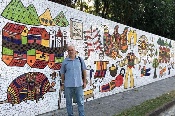 Peter Altman stops at a mural to martyred St. Oscar Romero, near the chapel where the archbishop was slain in 1980 in San Salvador. (M. Scherer-Emunds/El Salvador) Slug: El Salvador violence