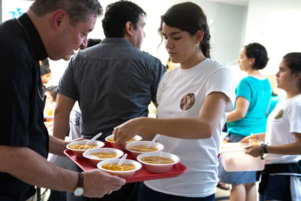 Reflection: With Refugees in El Paso- Bishop Robert J. Brennan, auxiliary bishop of Rockville Centre, N.Y., helps a volunteer at a Catholic Charities-run respite center in McAllen, Texas, serve soup July 1, 2018, to immigrants recently released from U.S. custody. A delegation of U.S. bishops has traveled to the Diocese of Brownsville, Texas, to learn more about the detention of Central American immigrants at the U.S.-Mexican border. (CNS photo/Chaz Muth