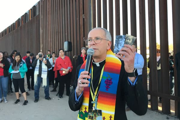 Bishop Mark J. Seitz of El Paso, Texas, holds photos of two migrant children who died in U.S. custody; he spoke during the Feb. 26 Interfaith Service for Justice and Mercy at the border near Sunland Park, N.M. (CNS photo/David Agren)