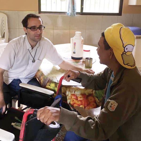 Ryan Thibert listens to a resident's concerns at a senior care center in Bolivia. (Courtesy of R. Thibert/Bolivia)