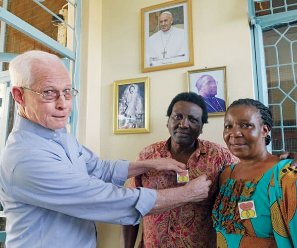 Maryknoll Father John Eybel, who as assistant pastor at Transfiguration parish in Mabatini assist with the church's holistic ministry, awards Marriage Encounter pins to Anton and Eugenia Msafiri. The couple had completed a Marriage Encounter weekend to help them strengthen their relationship.