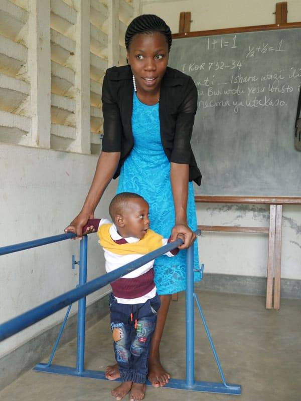 Edita helps her 2-year-old nephew Jordan with physical therapy at the Mabatini Public Health Center, a holistic ministry of Maryknoll-run Transfiguration parish in the Mabatini section of Mwanza, Tanzania.