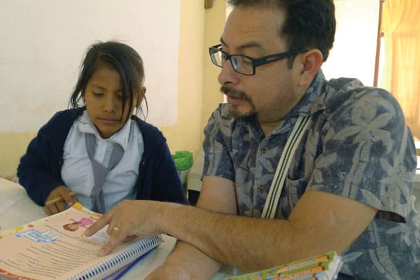 Deacon Leonel Yoque helps a little girl with homework at Apoyo Escolar program. Yoque, who is a member of the Maryknoll Discípulos Misioneros (Missionary Disciples) team, which sponsored the Maryknoll immersion trip to Bolivia. Photo by D. Aquije/Bolivia.
