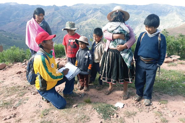 Gregorio Leon, a local health and education promoter, meets with the widow Evarista and her family to verify data to determine how his team can best assist them. (J. Siyumbu/Bolivia)