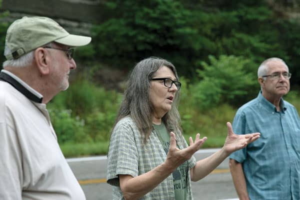 Elaine Tanner tells of her efforts to bring mining companies to court to clean up toxic waste that contaminates water, turning it orange. Tanner, flanked by Glenmary Father John Rausch, left, and Deacon Paul Bork, spoke to participants of an Appalachia immersion trip in Deane, Kentucky. Photo by O. Duran/U.S.