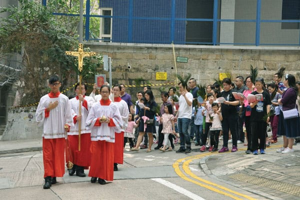 Evangelizing among skyscrapers - Our Lady of Mount Carmel parishioners share their Catholic faith in the streets of Hong Kong during Palm Sunday procession. (Courtesy of OLMC Church/Hong Kong)