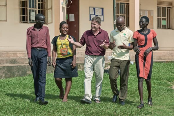 Maryknoll Lay Missioner Gabe Hurrish (c.) walks with students in Solidarity Teacher Training College, where he helps prepare future educators. (P. Jeffrey/S. Sudan)