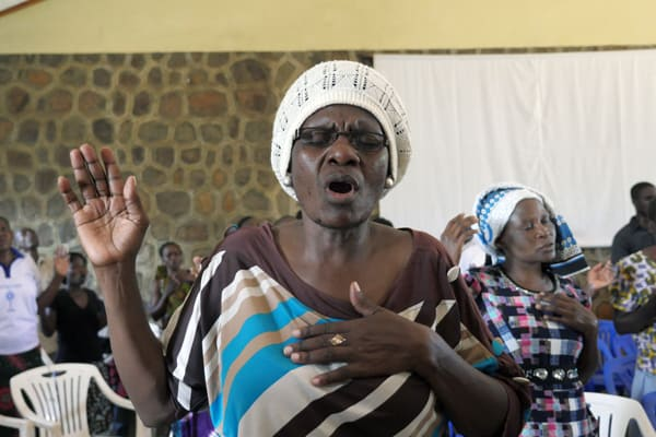 A woman prays at charismatic worship service at Transfiguration Catholic Church community center in the Mabatini neighborhood of Mwanza, Tanzania, one aspect of the holistic ministry at the Maryknoll-run parish.