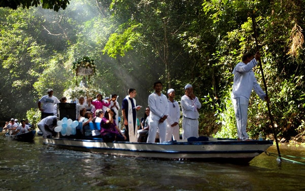 Amazonian faces of the Church: A priest holds a Bible as he leads pilgrims in prayer along during an annual river procession and pilgrimage on the Caraparu River in Santa Izabel do Para, Brazil, in this 2012 file photo. (CNS, P. Santos, Reuters/Brazil)