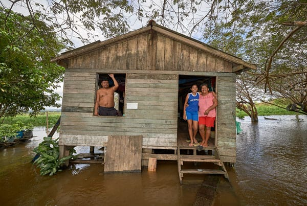 Amazonian faces of the Church: Juscelina Silva Batista (right), 54, her daughter Geovana Batista de Sousa, 11, and her partner Cantidio Rego, 69, stand in their home in the middle of the Amazon River near Santarem, Brazil. The family is one of the last holdouts in an area where land is being bought up to build a large port facility. (CNS, P. Jeffrey/Brazil)