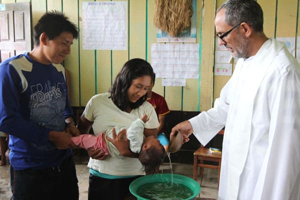 Amazonian faces of the Church: Spanish Augustinian Father Miguel Angel Cadenas baptizes an infant in an Urarina indigenous community on Peru's Urituyacu River June 6, 2014. (Barbara Fraser/ Peru)