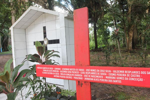 A red cross stands beside the grave of U.S.-born Sister Dorothy Stang in Anapu, Brazil, who was killed in 2005. The cross bears the names of 16 local rights activists who have been murdered since. (B. Fraser/Brazil)