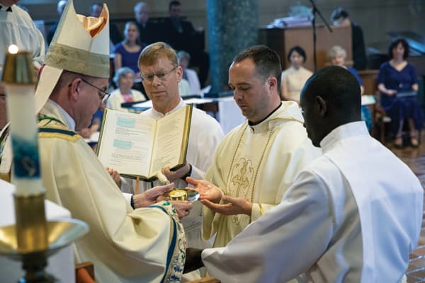 "Sent Forth to Serve in Mission: Bishop John Barres of Rockville Centre, N.Y., presiding prelate, anoints the new priest's hands, praying ""that you may sanctify the Christian people and offer sacrifices to God."""