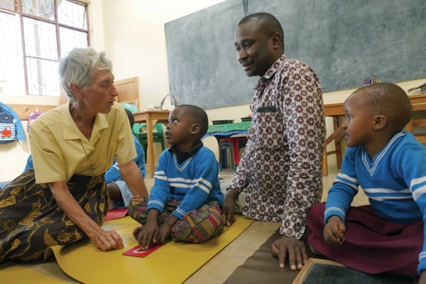 At the Mercy Montessori school, located on the church property of Sacred Heart of Jesus parish in the Ilemela section of Mwanza, Tanzania, Sister Celeste Darr and the parish pastor, Father Pamphilias Madata, join some of the pupils in a learning exercise. Founded by Sister Derr, the school focuses on education with a gentle and compassionate touch. Photo by Sean Sprague/Tanzania