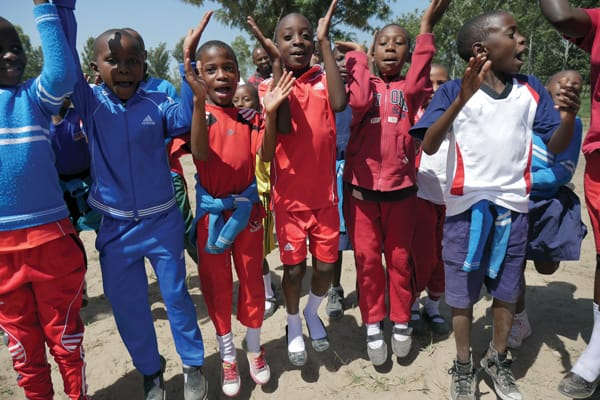 A group of students who attend Mercy Montessori elementary school in the Igombe section of Mwanza, Tanzania, jump for joy during an outdoor school assembly. Founded by Maryknoll Sister Celeste Derr, the school focuses on education with a gentle and compassionate touch. Photo by Sean Sprague/Tanzania