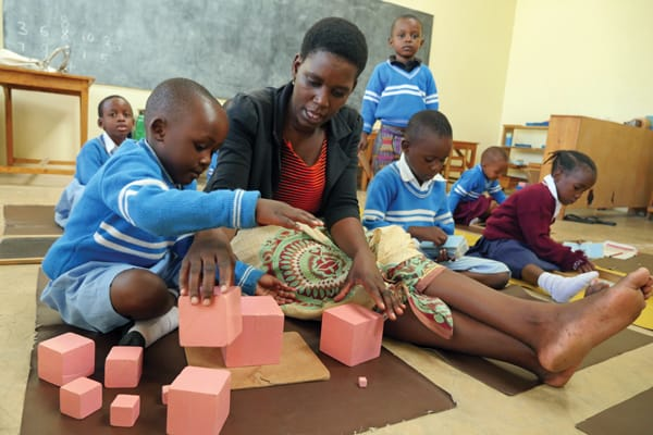 Teacher Anna John helps students develop coordination and motor skills in a preprimary class at Mercy Montessori School in the Ilemela section of Mwanza. The school, founded by Maryknoll Sister Celeste Derr, focuses on education with a compassionate touch.Photo by Sean Sprague/Tanzania)