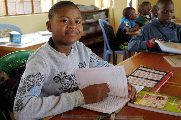A student at Mercy Montessori School in the Igombe section of Mwanza, Tanzania, looks up from her studies. The school was founded by Maryknoll Sister Celeste Derr. Photo by Sean Sprague/Tanzania