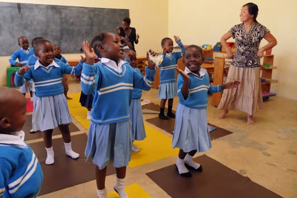 Guadalupe Petro, right, a Maryknoll lay missioner, leads pupils of the Mercy Montessori School in a lesson that is reinforced with song and dance. The school, founded by Sister Celeste Derr in Mwanza, Tanzania, emphasizes education with a gentle and compassionate touch. Photo by Sean Sprague/Tanzania.
