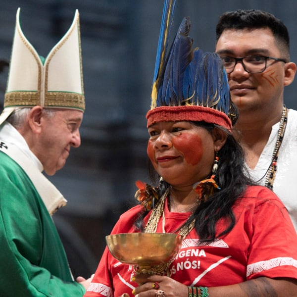 An indigenous woman in a feathered headdress presents an offertory gift as Pope Francis celebrates the opening Mass of the Synod of Bishops for the Amazon in St. Peter's Basilica at the Vatican Oct. 6, 2019. Some bishops say indigenous culture can enrich Catholic liturgy. (CNS/Vatican Media)