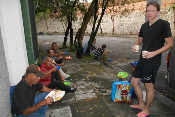 Tim Ross serves coffee to homeless men outside the La Carpa Catholic Worker hospitality house in San Salvador's Barrio San Miguelito. (Erica Olson/El Salvador)