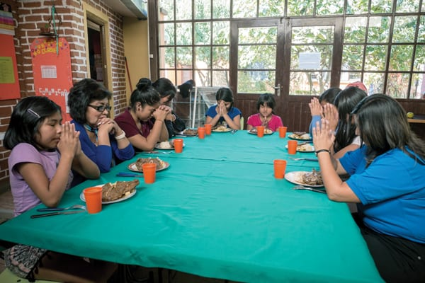 At lunchtime in Hogar Nuestra Casa shelter in Cochabamba, the girls, accompanied by staff members, say grace before eating a meal they have helped prepare. (Nile Sprague/Bolivia)