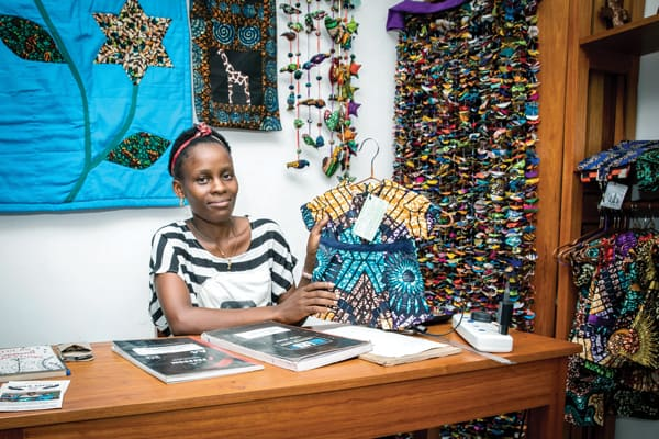 Beatrice shows the products made by people at Uzima Centre at the Vipaji Vyetu store in Mwanza. The store also sells crafts from other church-based charitable organizations. (J. Fleury/Tanzania)