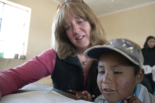 As a Maryknoll lay missioner in Amachuma, Maggie Fogarty helps a young neighbor with his schoolwork as he and modern shepherds in Bolivia reflect the face of God to her. (S. Sprague/Bolivia)