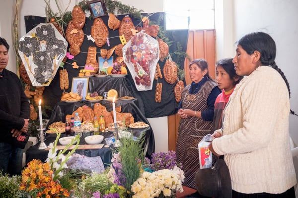 Visitors and Aymara residents of Jayllihuaya, including Father Cookson, gather at the house of the Flores family to pray for their deceased relatives and honor their memory. (N. Sprague/Peru)
