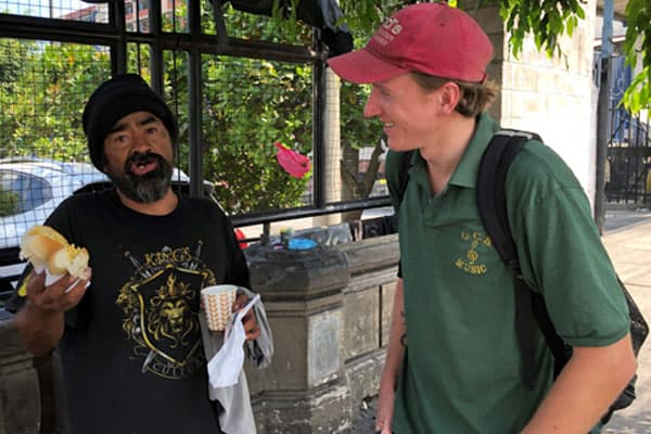 Tim Ross, right, talks with Louis, who is homeless in El Salvador, as the Maryknoll lay missioner completes a bread-and-coffee route near the general hospital in San Salvador. (Meinrad Scherer-Emunds/El Salvador)