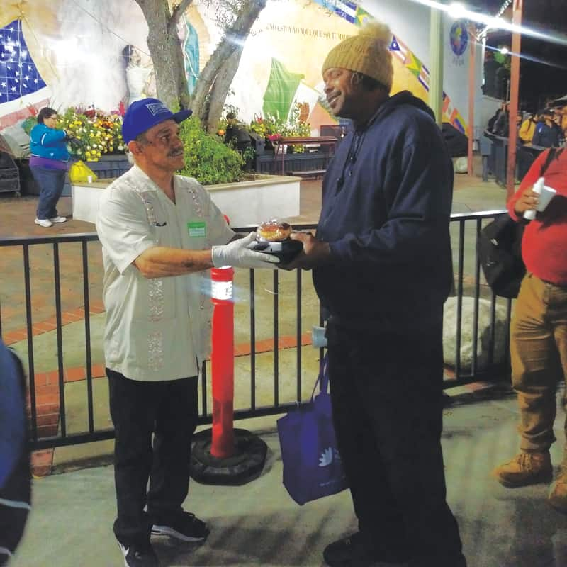 LA homelessness: As a volunteer now, Jose Lopez (left) serves food to homeless people at the Church of Our Lady Queen of the Angels.