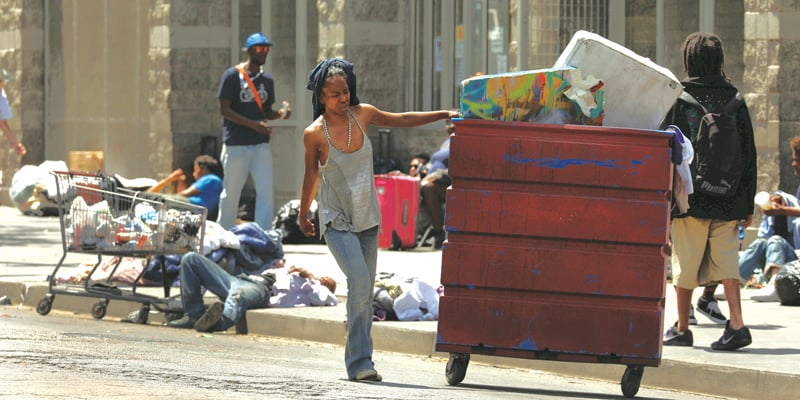 LA Homelessness: A woman (at left) pushes a cart with her belongings in downtown Los Angeles.