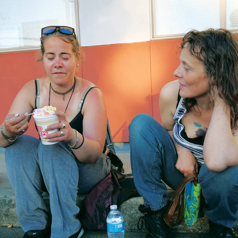 Two homeless women chat on the street and eat food from MercyWatch. (Peter Saunders/U.S.)