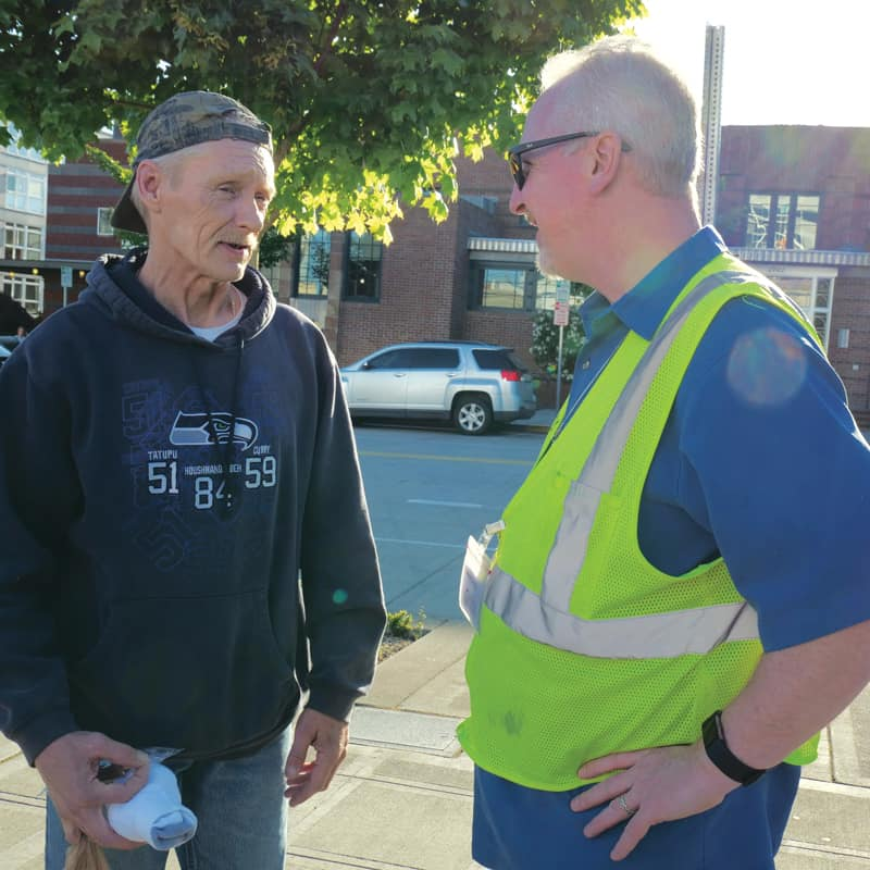 Deacon Dennis Kelly, right, talkes with Lonny, a homeless man recovering from opioid addiction. (Peter Saunders/U.S.)