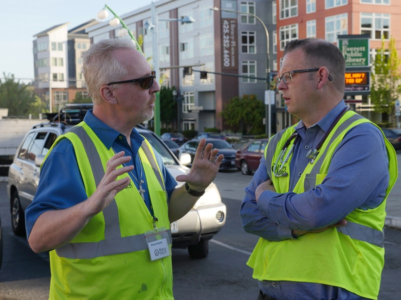 Deacon Dennis Kelly, left, a Maryknoll deacon partner, discusses the work of MercyWatch to help the homeless with fellow volunteer Dr. Jimmy Grierson, a family medical physician. (Peter Saunders/U.S.)