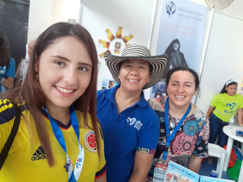 Maryknoll Sisters Nena Heramil (center) and Norma Pocasangre (right) smile with a World Youth Day pilgrim who visited their vocation booth. (Courtesy of the Maryknoll Sisters/Panama)