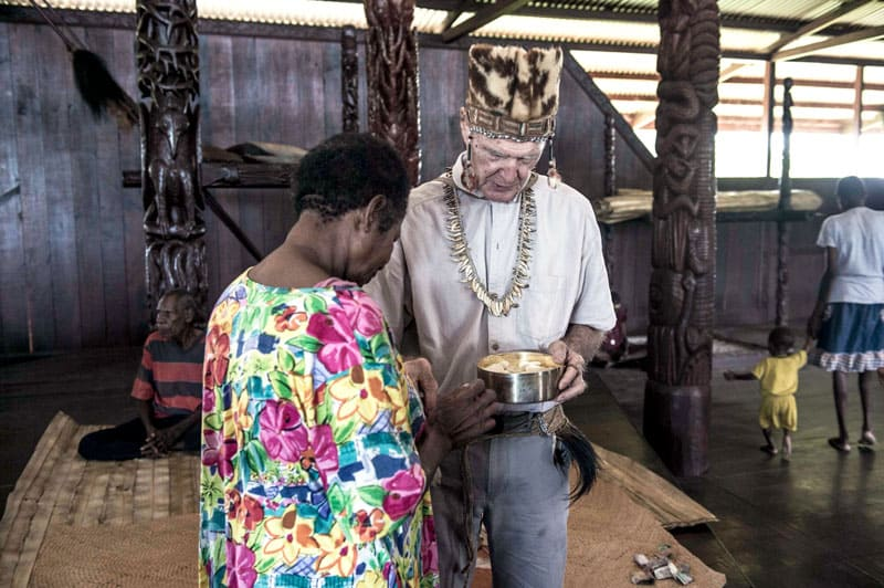 Maryknoll Father Vincent Cole gives Holy Communion to Sabina Totiniap, an Asmat indigenous woman who helps him. Photo by Joshua Irwandi/Indonesia