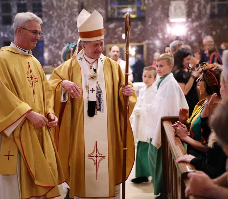 After World Mission Sunday Mass at St. Ferdinand Church, pastor Father Jason Torba and Cardinal Blase Cupich greet the congregation, including all those who do mission in Chicago. (Julie Jaidinger, Chicago Catholic/U.S.)