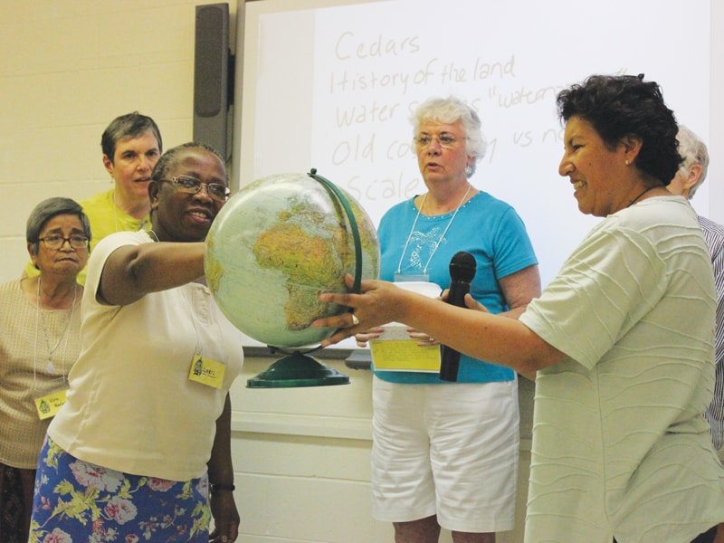 Maryknoll Sisters Claris Zwareva (l.) and Rosalva Sandi hold a globe during a discussion on bioregional theology at the Maryknoll Mission Institute. (Courtesy of Maryknoll Sisters/U.S.)