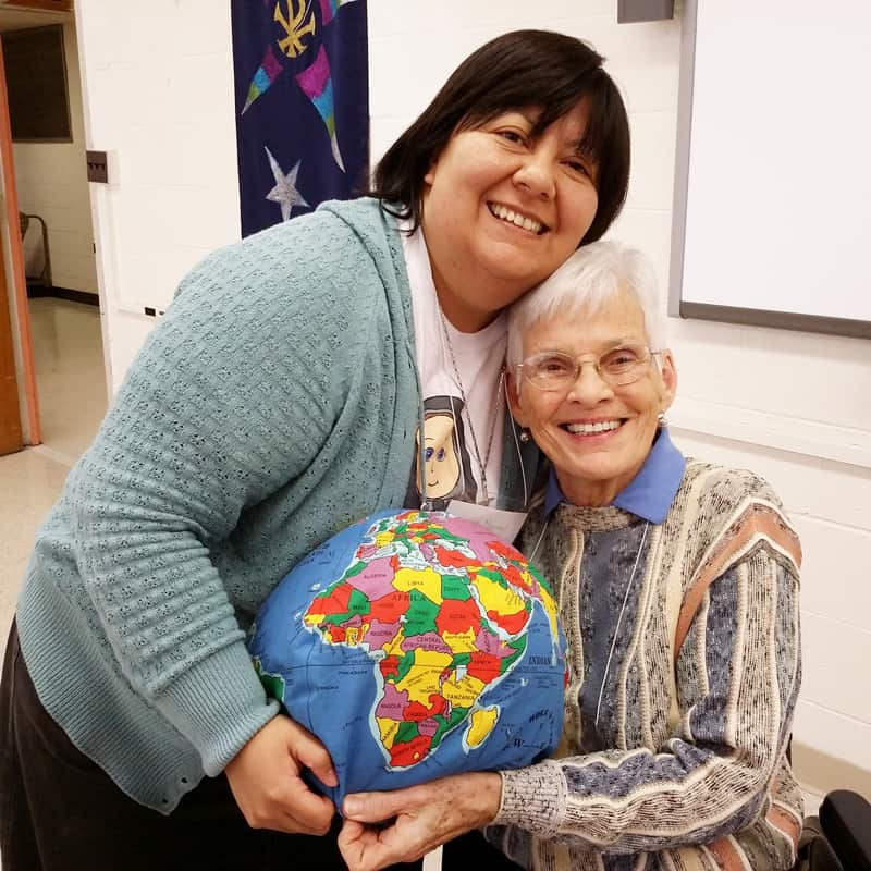 At the Maryknoll Mission Institute, a program presenter, Judy Mayotte (right), gets a hug from participant Sister Martha Lopez, a Missionary Sister of the Sacred Heart. (Courtesy of Maryknoll Sisters)